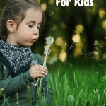 Vermicomposting For Kids girl blowing on a dandelion.