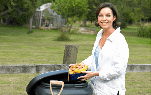 Vermicompost Project lady with a worm bin feeding organic waste