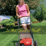 Woman mowing the grass with a push mower.